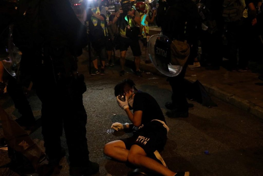 A protester lies on the ground amid a group of riot police during the dispersal of an unsanctioned rally in Yuen Long on Saturday. Photo by Samantha Mei Topp.