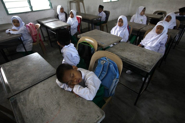 A student sleeps inside a classroom during the first day of school at an islamic local school in Kuala Lumpur on January 4, 2012. — AFP pic