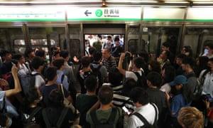Train passengers wait as protesters disrupt train services at Tiu Keng Leng station in Hong Kong.