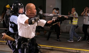 A police officer points a shotgun at protesters in Hong Kong.