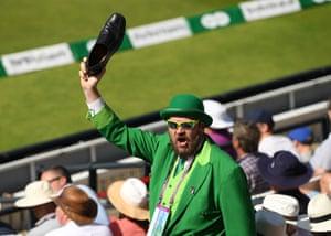 An Ireland fan celebrates runs by waving his shoe.