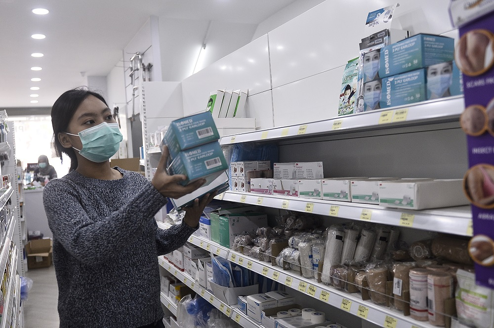 A sales assistant arranges boxes of face masks at a Pharmhouse Pharmacy outlet in Setia Alam January 28,2020. — Picture by Miera Zulyana