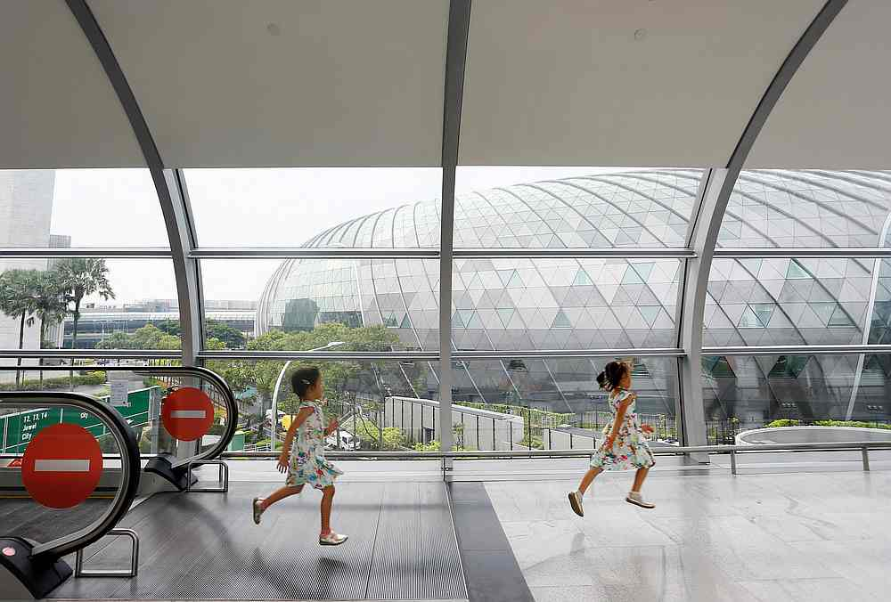 Children run through a walkway that links the various terminals to Jewel Changi Airport in Singapore, April 11, 2019. The republic's economic growth slowed to  0.7 per cent in 2019. — Reuters pic