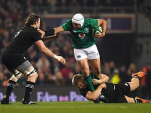 Rory Best powers through two All Black tacklers during Ireland's 2018 victory in Dublin.