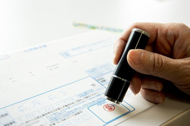 © Bloomberg. A hanko is stamped on a banking document in an arranged photograph taken in Tokyo, Japan, on Tuesday, Feb. 12, 2019. Hanko, the personal stamps required for even simple transactions in Japan since the 1800s, are getting phased out at some of the country's biggest financial institutions. Photographer: Keith Bedford/Bloomberg