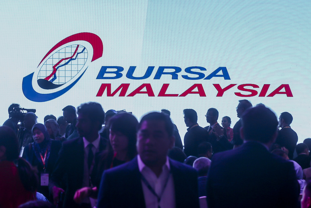 The silhouettes of attendees are seen in front of a screen with the Bursa Malaysia logo at Invest Malaysia 2019 in Kuala Lumpur March 19, 2019. — Picture by Firdaus Latif