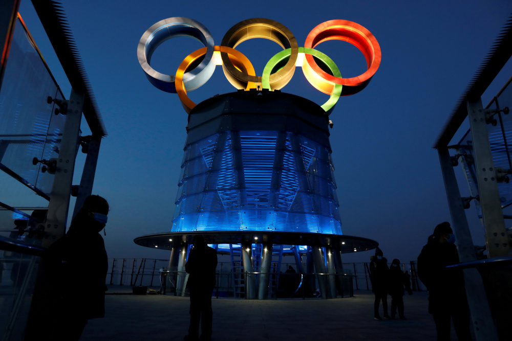 People wearing face masks are seen near the lit-up Olympic rings at top of the Olympic Tower, a year ahead of the opening of the 2022 Winter Olympic Games, in Beijing, China February 4, 2021. — Reuters pic