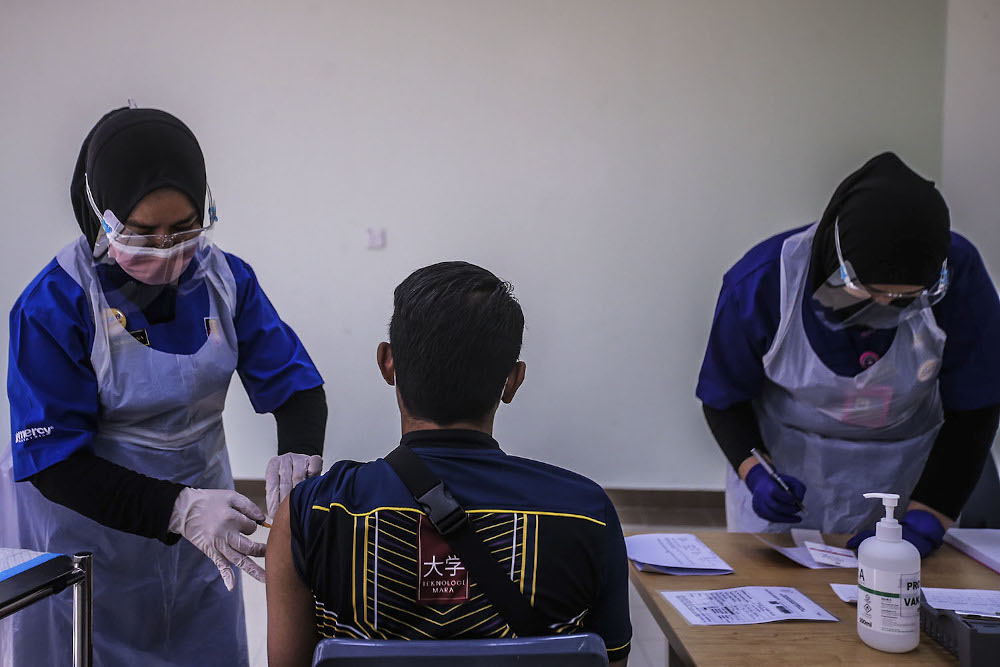 A healthcare worker administers a dose of the Pfizer-BioNTech Covid-19 vaccine to a frontliner at the UiTM Private Specialist Centre in Sungai Buloh March 2, 2021. ― Picture by Hari Anggara