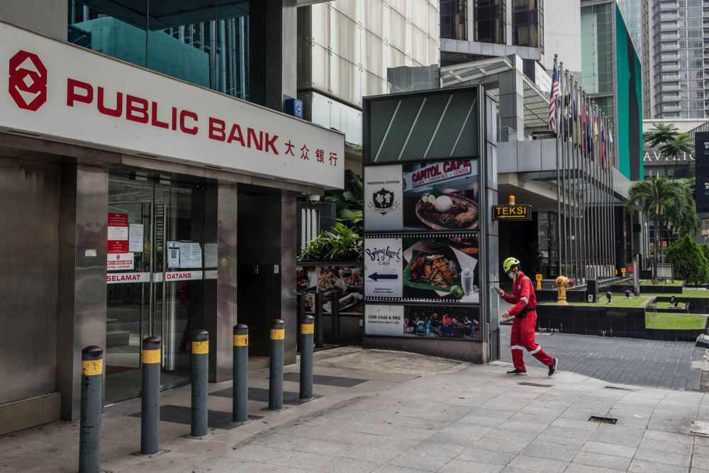A pedestrian walks past a Publc Bank branch in Kuala Lumpur July 9, 2021. — Picture by Firdaus Latif