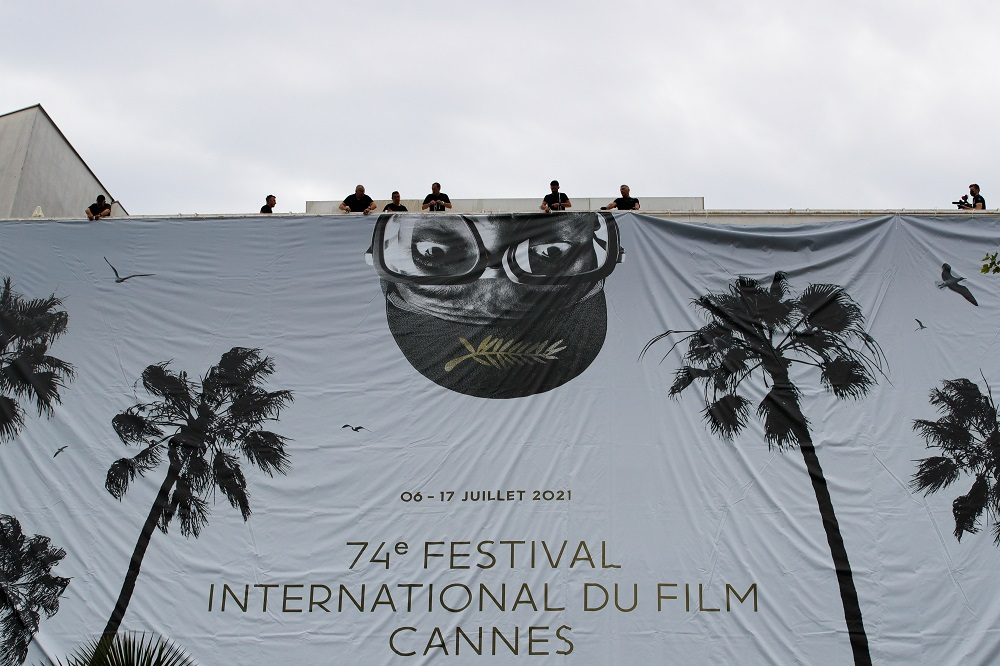 Workers set up a giant canvas of the official poster featuring Spike Lee on the facade of the festival palace, ahead of the opening ceremony of the 74th Cannes Film Festival, in Cannes July 4, 2021. — Reuters pic