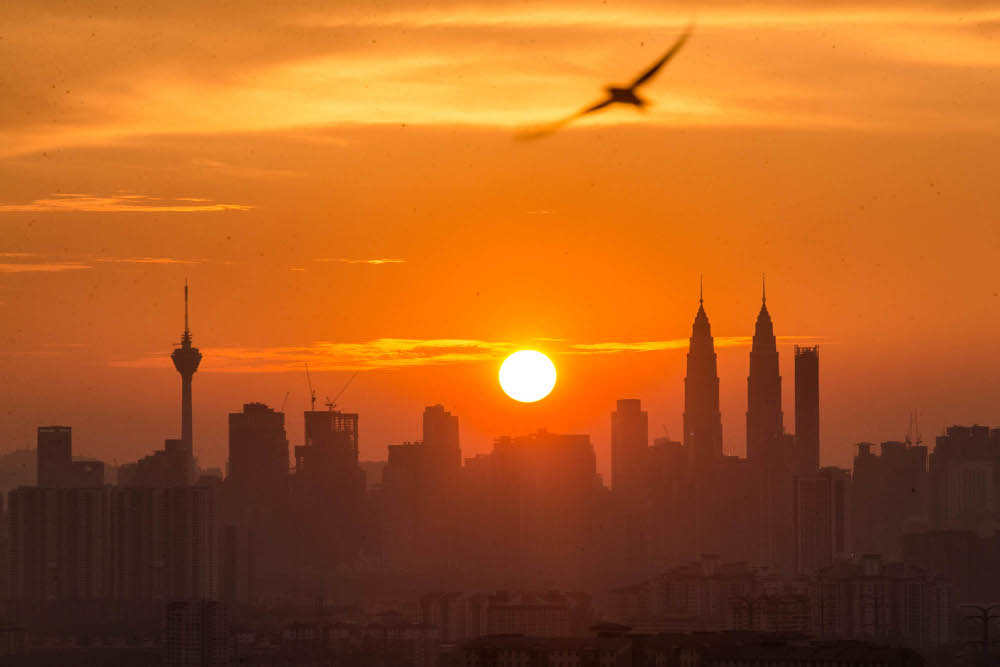 Malaysia's landmark Petronas Twin towers and Kuala Lumpur Tower are seen as the sun sets over the Kuala Lumpur skyline in Ampang July 20, 2021. — Picture by Firdaus Latif