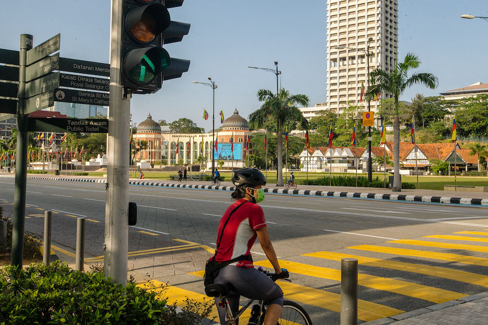 People are seen cycling along Dataran Merdeka in Kuala Lumpur February 21, 2021. Datuk Seri Ismail Sabri Yaakob said individual sports like cycling around the neighbourhood is allowed, on condition that cyclists keep a distance of two to three metres from each other. — Picture by Firdaus Latif