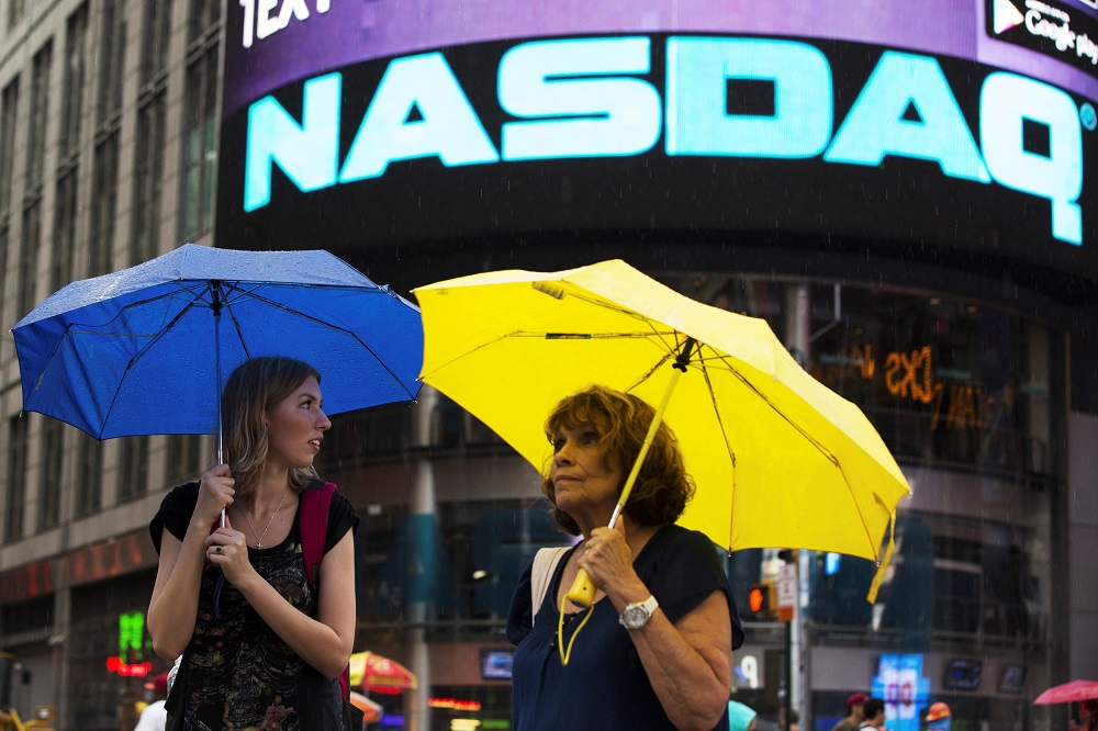 Two women hold umbrellas as they walk past the Nasdaq MarketSite in New York's Times Square August 22, 2013. — Reuters pic