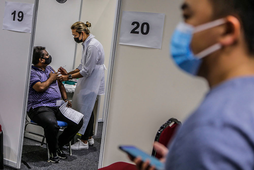 Walk-in vaccine recipients receive their Covid-19 jabs at the Kuala Lumpur Convention Centre vaccination centre, August 2, 2021. ― Picture by Hari Anggara