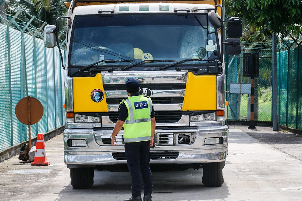 A Road Transport Department officer inspects the weight of a lorry at the Road Transport Department Enforcement Station in Penaga July 23, 2020. — Picture by Sayuti Zainudin
