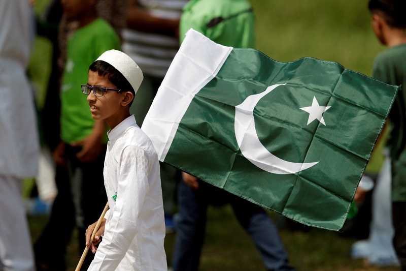 A boy holds a national flag as he watches an air show to celebrate the 70th Independence Day in Islamabad August 14, 2017. — Reuters pic