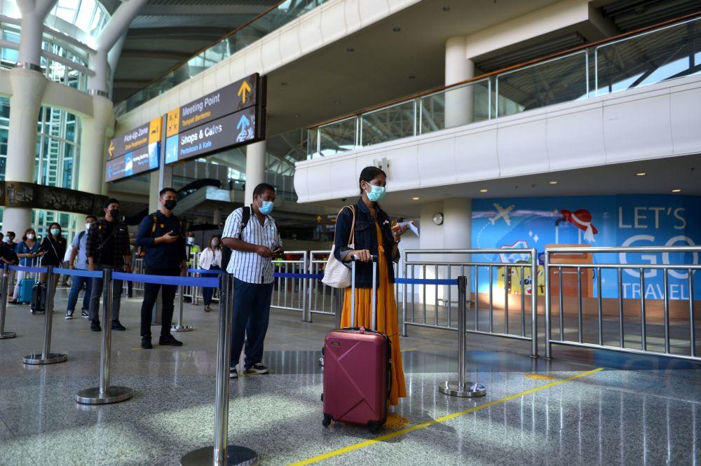 Passengers stand in line at Ngurah Rai International Airport in Badung, Bali, Indonesia October 9, 2021. — Reuters pic