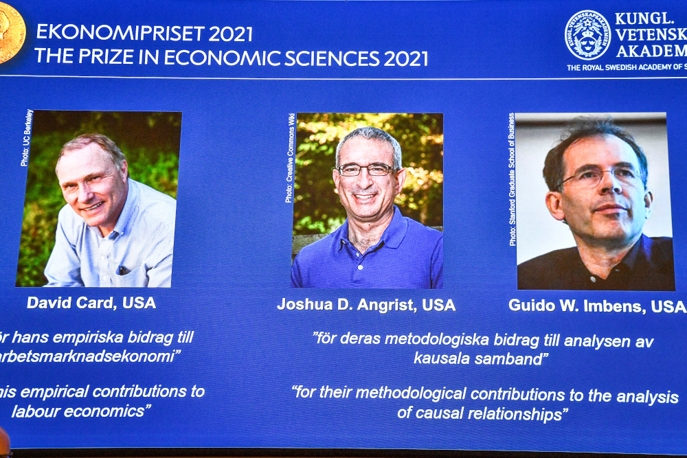 Photographs of the 2021 Nobel economics prize winners David Card, Joshua Angrist and Guido Imbens appear on a screen during the announcement of the award in Stockholm October 11, 2021. — Claudio Bresciani/TT News Agency pic via Reuters